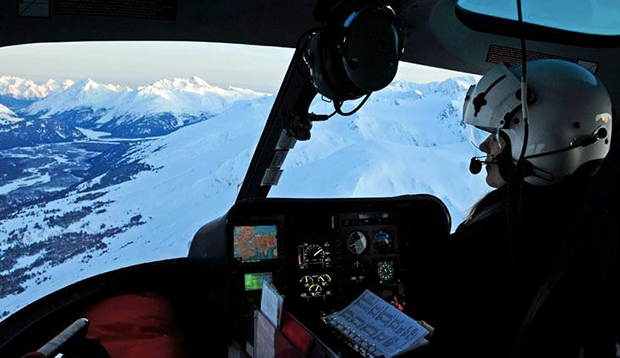 Lorena Knapp in the cockpit of her helicopter with Alaska scenery outside