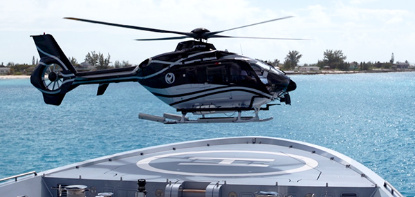Helicopter landing on forward helideck of private superyacht