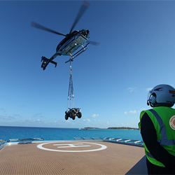 Helicopter lifting quad bike off luxury yacht