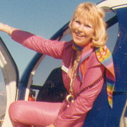 Rosemary Arnold sporting a pink flight suit in a Hughes 500